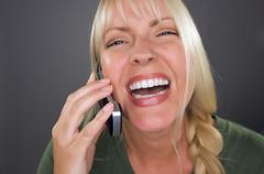 Joyful Blond Woman Using Cell Phone Against a Grey Background. - stock photo