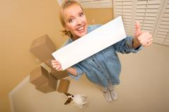Woman and Doggy with Blank Sign Near Moving Boxes - stock photo