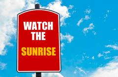 Watch The Sunrise motivational quote written on red road sign Stock Photos