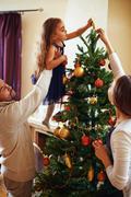 Decorating xmas tree together - stock photo
