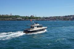 Small boat cruises the Golden Horn - stock photo