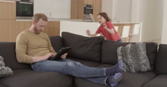 Girl dives onto sofa to look at tablet with dad in contemporary modern home, Stock Footage