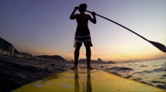 Teenager paddling on Stand Up board in slow motion - stock footage
