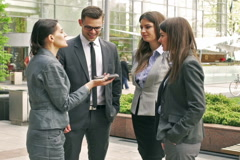 Businesspeople standing outside and talking on cellphone - stock footage