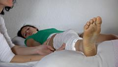 Therapist leg massage of beautiful girl with gyps on broken leg lying at hosp Stock Footage