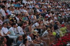 The audience are watching a tennis match - stock photo