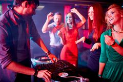 Deejay and pretty dancers - stock photo