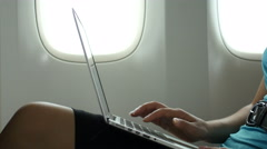 Stock Video Footage of Female passenger using laptop on airplane, close up