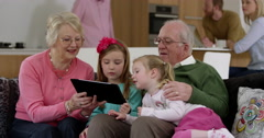 Grandparents play game on electronic tablet with grand daughters in beautiful Stock Footage