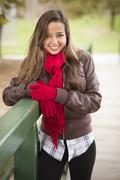Pretty Festive Smiling Woman Portrait Wearing a Red Scarf and Mittens Outside - stock photo