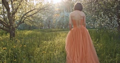 Beautiful young woman wearing elegant orange dress Stock Footage