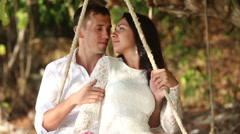 Groom and bride roll on rope swing and join hands on beach Stock Footage