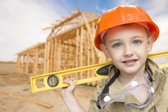 Child Boy Dressed Up as Handyman in Front of New House Framing. - stock photo