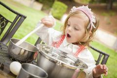 Happy Adorable Little Girl Playing Chef Cooking in Her Pink Outfit. Stock Photos