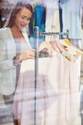 Choosing blouse in boutique - stock photo