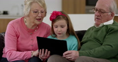 Grandparents play game on electronic tablet with grand daughter in beautiful Stock Footage