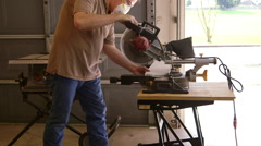 Woodworker using a power miter saw to cut a board Stock Footage