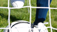 Soccer player ties his football boots, football net in front Stock Footage