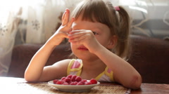 Girl with raspberries on fingers Stock Footage