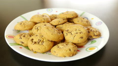 Hand takes a cookie from a plate on a table, the other disappear one by one - stock footage