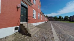 Walking on cobblestones  along an old red building Stock Footage