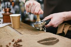 Grinding coffee beans - stock photo