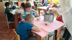 Nanny pours beverage for kids. Preschool children have a lunch in nursery school - stock footage