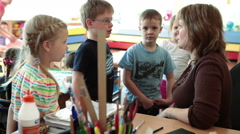 Kids talking with woman a teacher in classroom of kindergarten Stock Footage