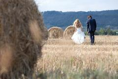 Married couple relaxing on a field with hay bales, feeling free and in love. Stock Photos