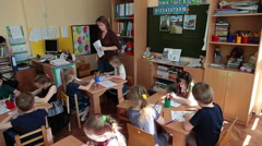 Preschool children drawing at the brain game with assistant help in daycare  - stock footage