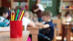 Pencil-box with color pencils in daycare children center, kids are in classroom Stock Footage