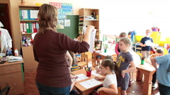Nursery educator and children have skill lesson in classroom Stock Footage