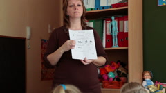 Woman educator in daycare center gives a lesson while standing near blackboard  Stock Footage