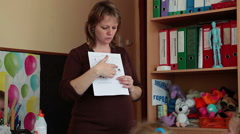 Female teacher explains the task while shows picture on paper sheet Stock Footage