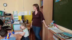 Woman educator of day-care center helps children to paint at lesson - stock footage