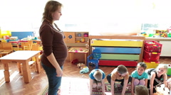 Educator in daycare center explains the rules of the game for children - stock footage