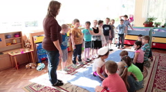Activities organizer plays the game with children in classrom Stock Footage