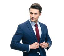 Confident businessman putting on suit jacket - stock photo