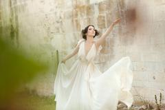 Beautiful woman in white long dress assuming a ballet position Stock Photos