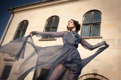 Elegant woman, in long transparent dress, posing in a graceful attitude. - stock photo
