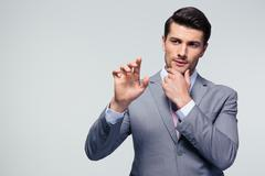 Pensive businessman touching a blank invisible screen Stock Photos