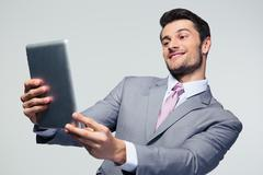 Happy businessman looking at tablet computer - stock photo