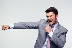 Businessman fighting over gray background - stock photo