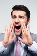 Businessman shouting over gray background Stock Photos