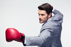 Businessman ready to fight with boxing gloves - stock photo