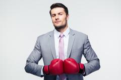 Businessman standing with boxing gloves - stock photo