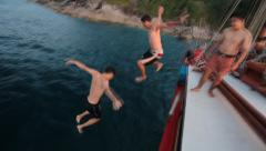Jumping off boat young people slow motion Stock Footage