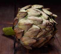 Ripe artichoke on a wooden table close up Stock Photos