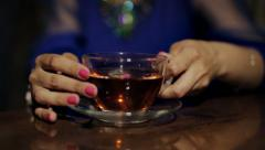 Girl in a blue dress drinks tea from a transparent cup Stock Footage