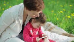 Mother and her daughter playing with phone during picnic in garden. Close-up Stock Footage